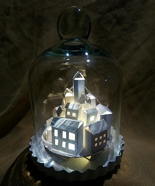 Kleine Stadt mit Trafo-Häuschen unter einer Glasglocke